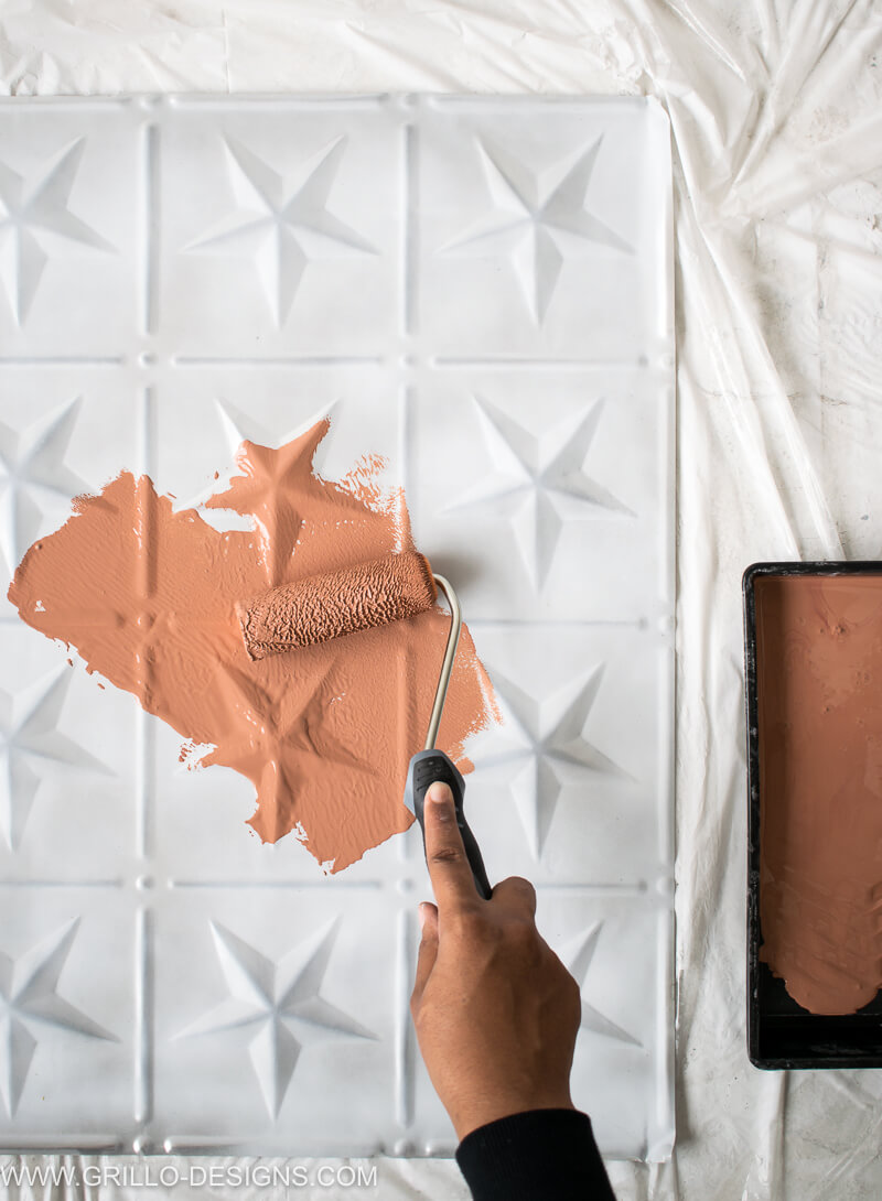 Apply paint to the tin tiles using a foam roller