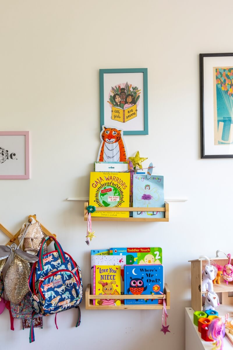 IKEA spice racks used as bookshelves for kids book. Hanger to the side is used to hold girls bags