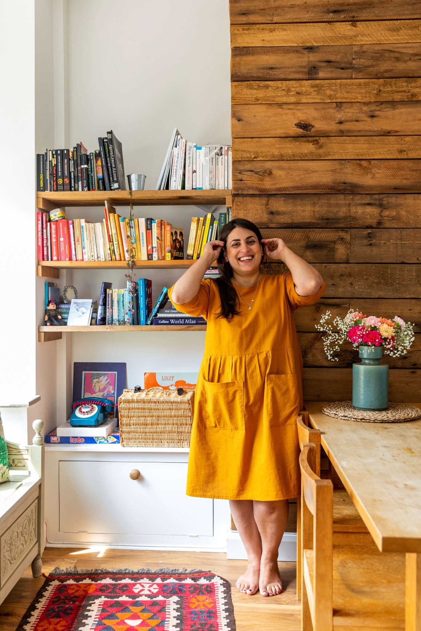 Rida is standing in front of the bookshelf wearing a mustard yellow dress and laughing