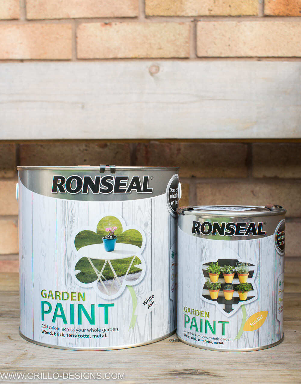 Two cans of outdoor ronseal color presented on a wooden surface