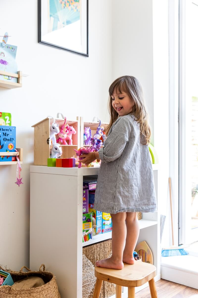 Girl standing on wooden stool and playing with toys on ikea kallax shelf. Her head is to the side and she is sticking her tongue out