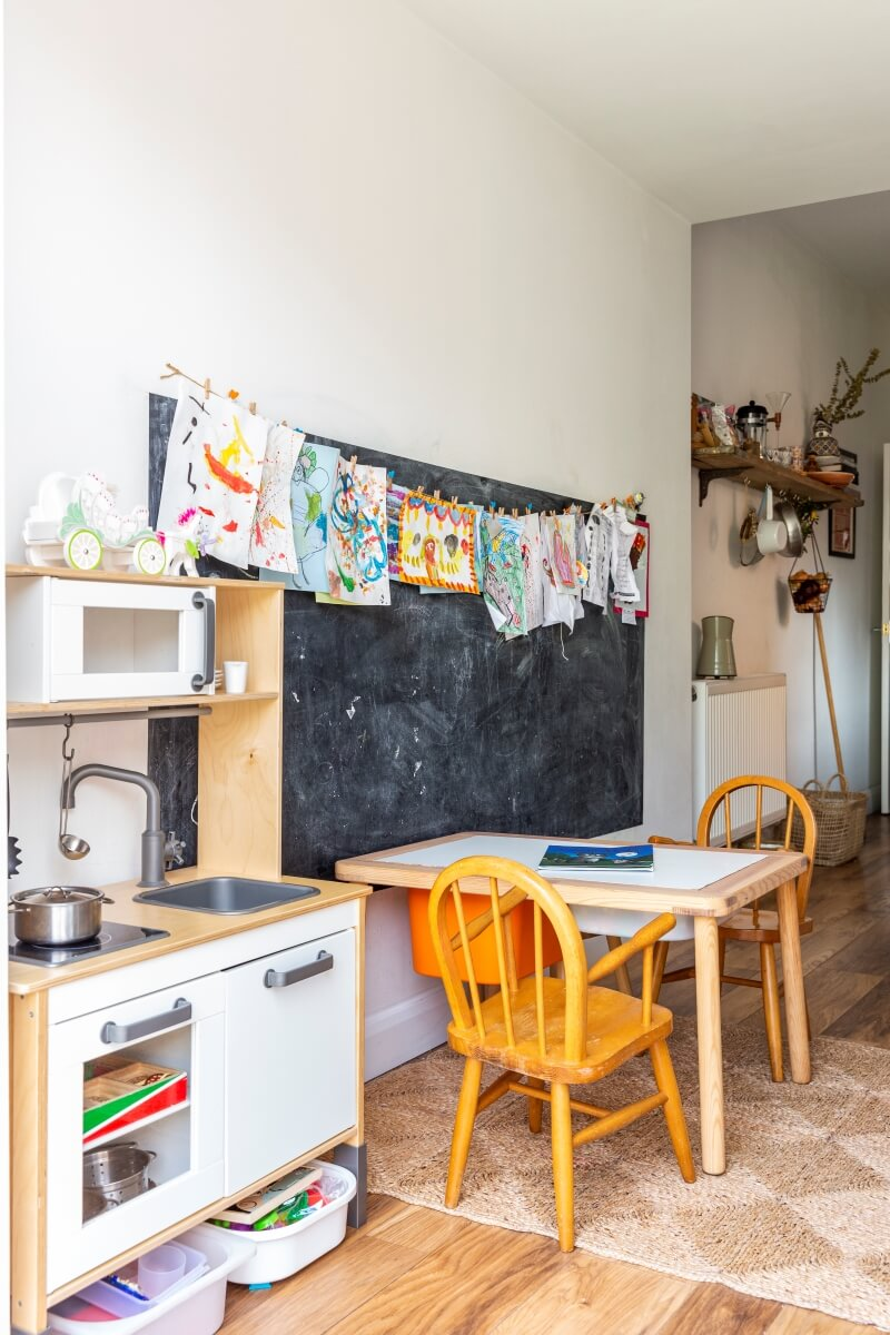 Kids play area in the kitchen. Ikea desk with two toddler chairs are seen against a painted blackboard wall