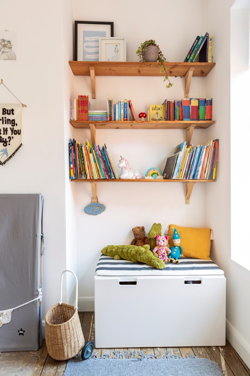 Wall shelves in alcove of rented kids room with ikea storage seat underneath. Shelves contain childrens books.