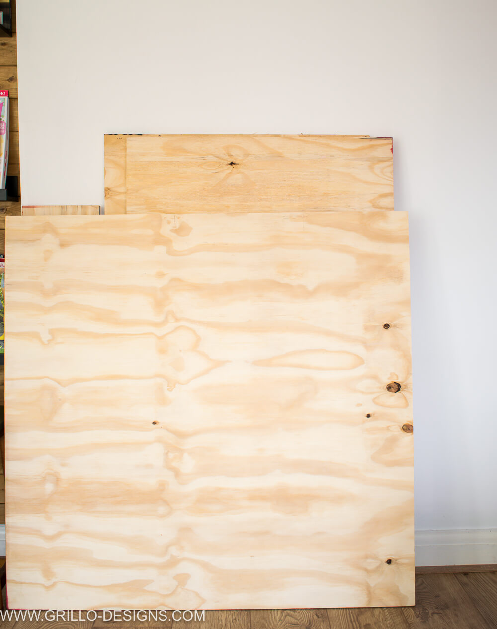 Plywood sheet propped up against a white wall
