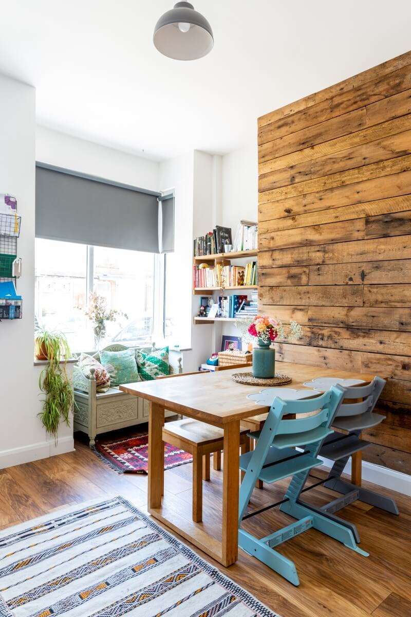 Side angle of dining room with rustic wooden paneled wall