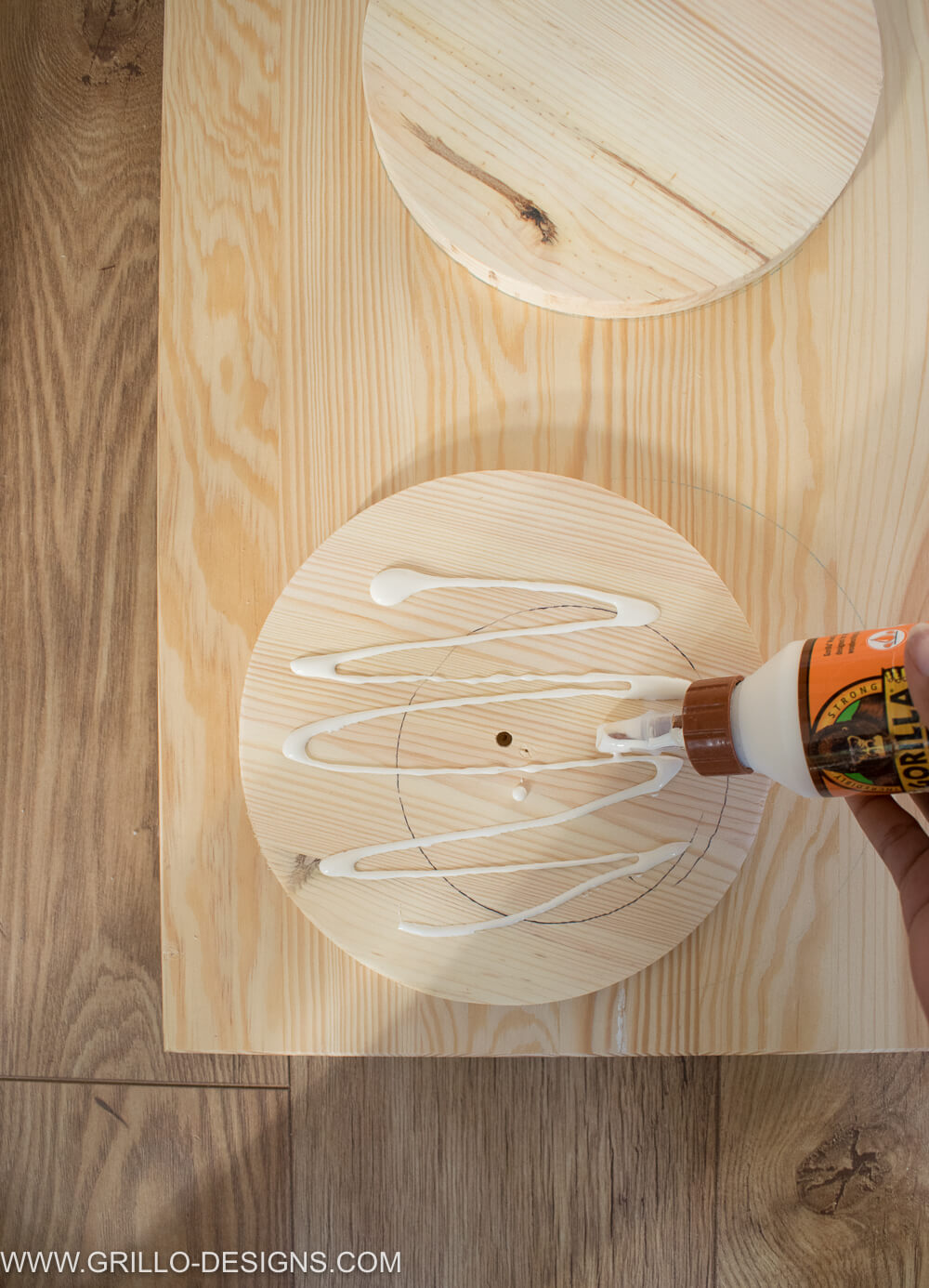 Apping wood glue to the back of the circles before sticking to the pine door