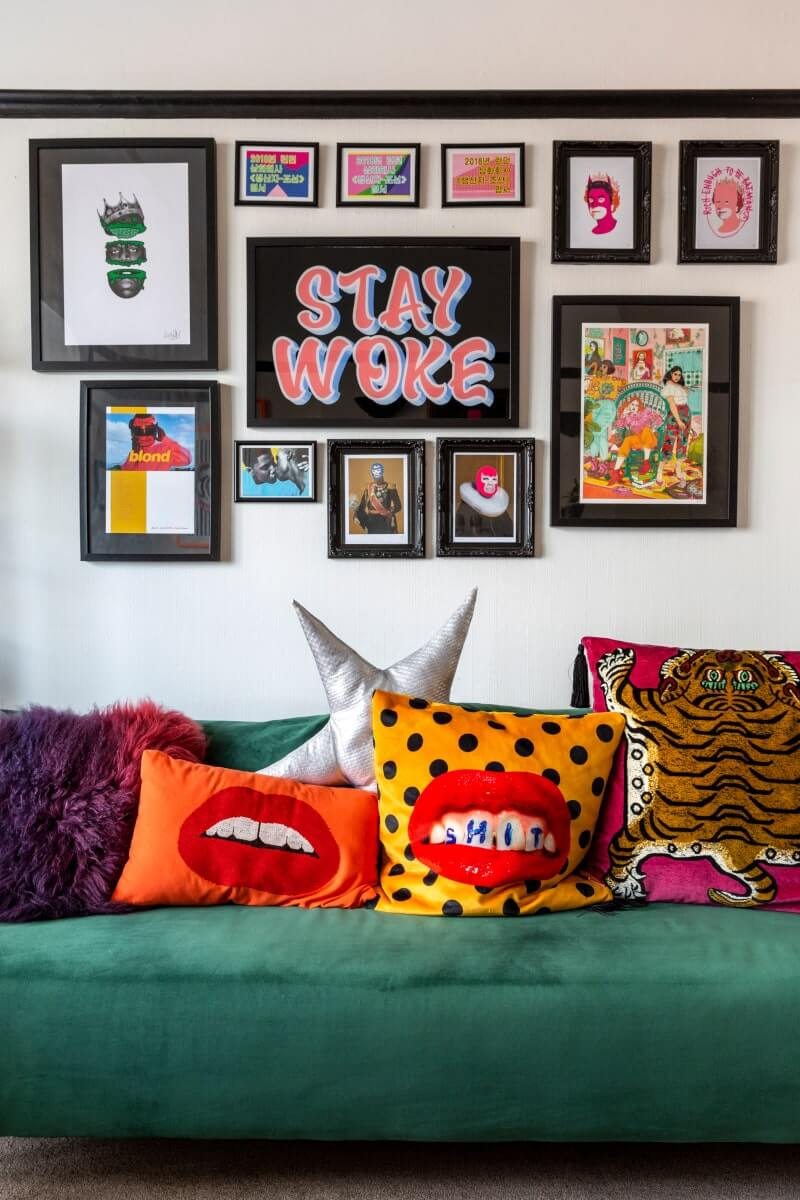 Colourful cushions places on green velvet sofa below a gallery wall
