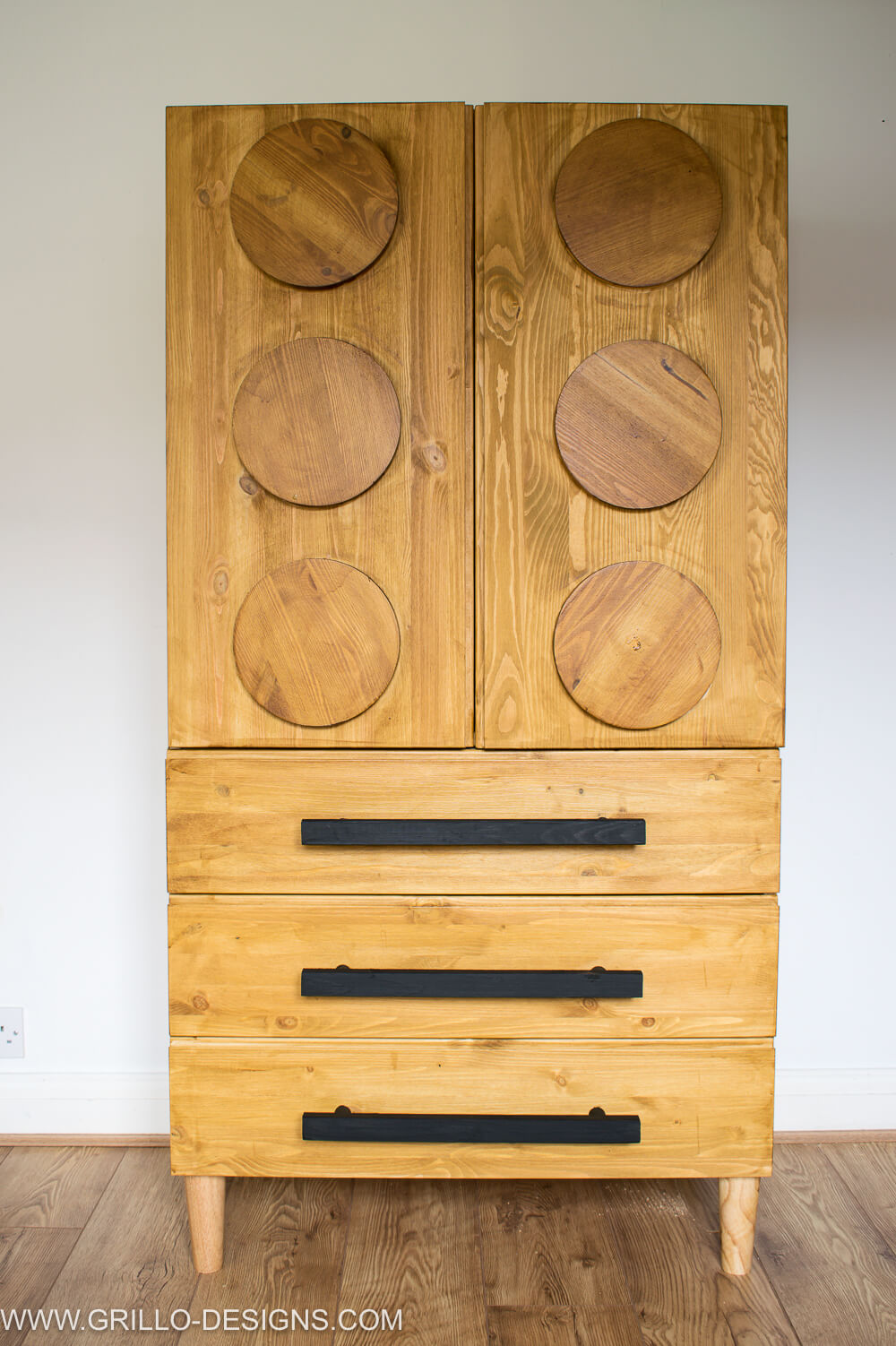 Black handles placed on the drawers of the wooden lego inspired wardrobe