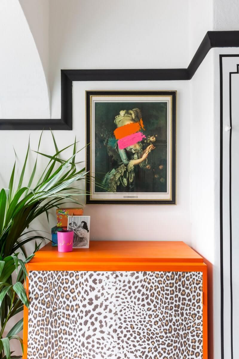 Leopard print dresser below a vintage frame