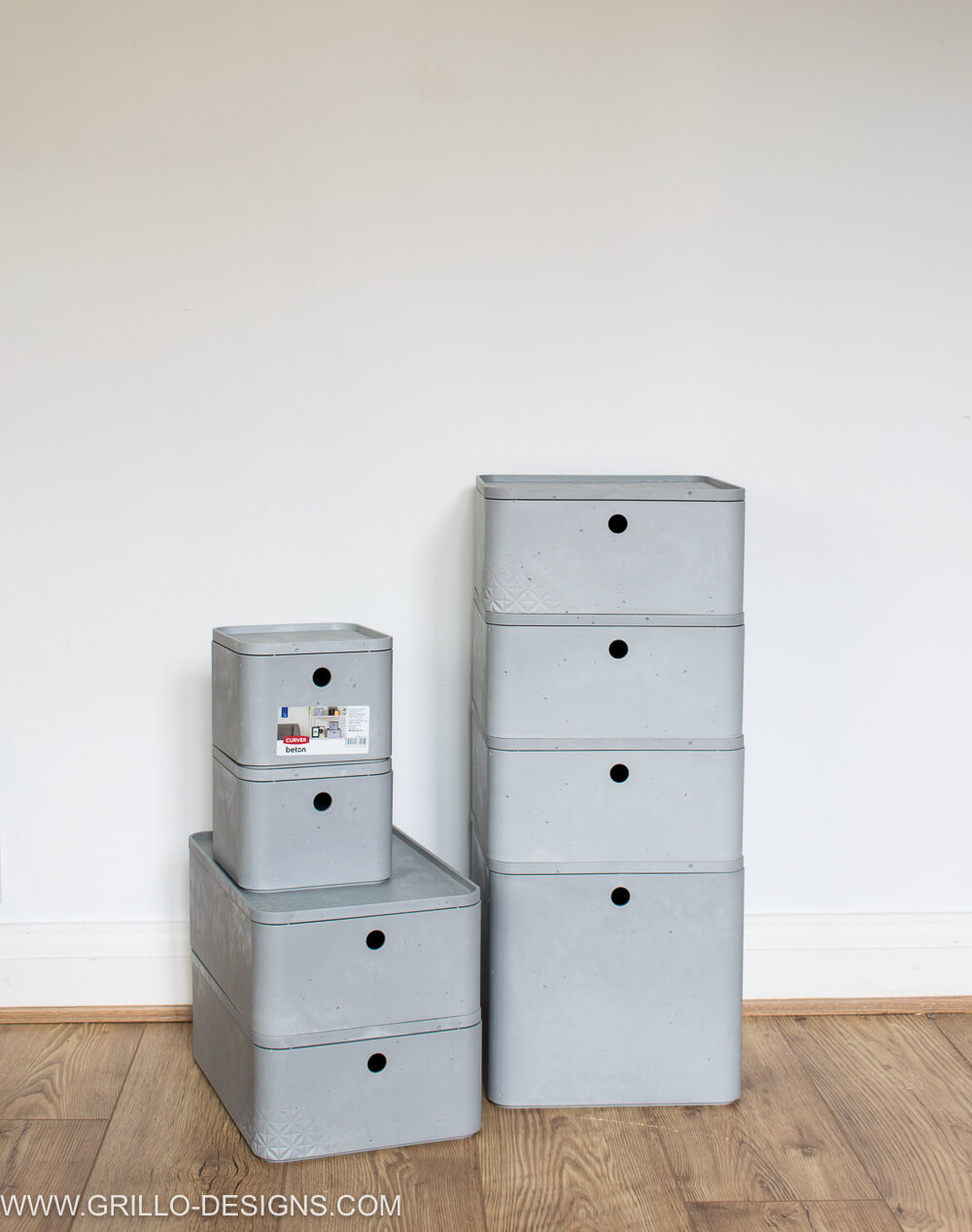 Image of curver boxes stacked on top of each other on the laminate flooring , against a white wall