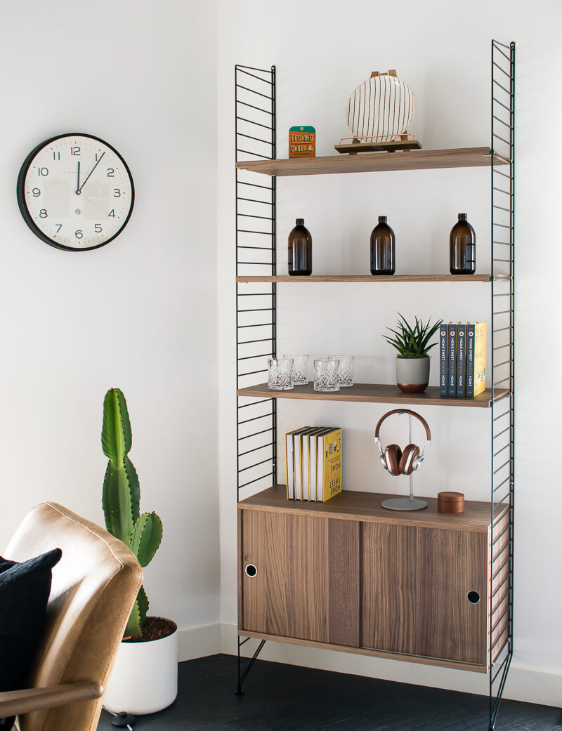 Industrial style rustic shelving styled with home sweet rented home books, bottles and plants