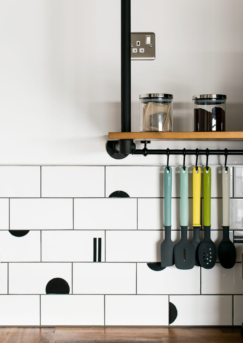 coloured Utensil hang underneath rustic wall shelving in kitchen