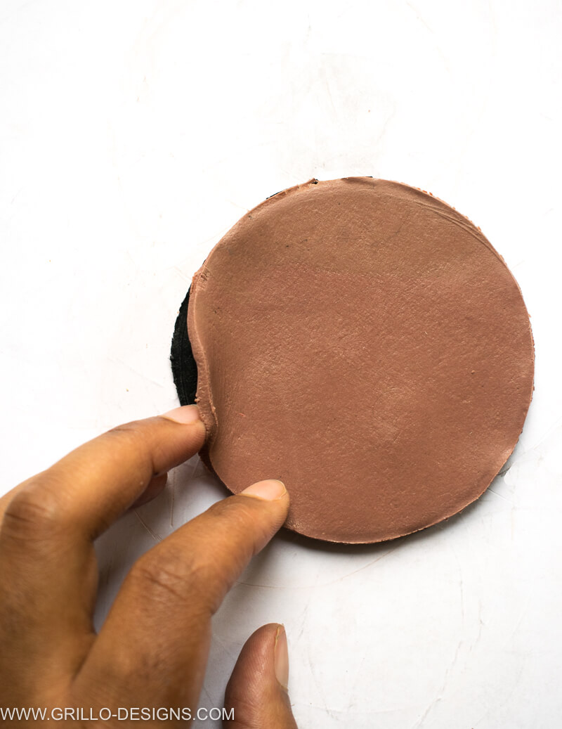 circle from leather nut clay placed on top of the black clay circle