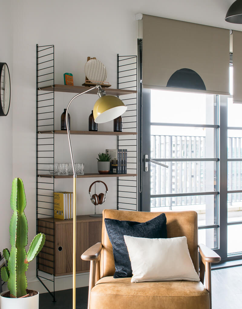 View of arm chair in front of the wire industrial shelving next to a large cactus
