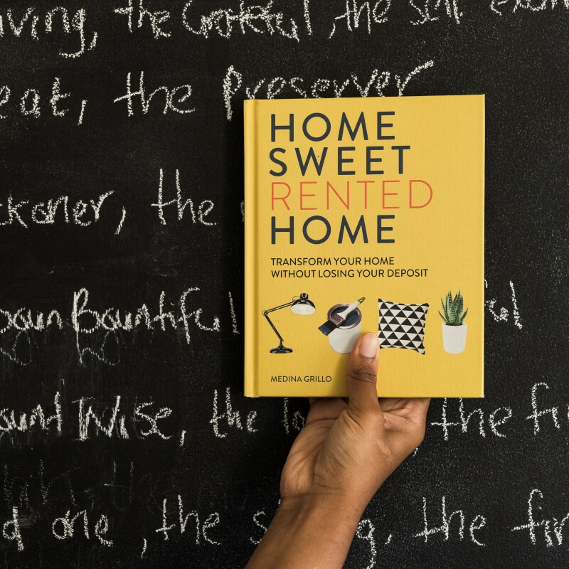 Home sweet rented home book help up against a chalkboard wall