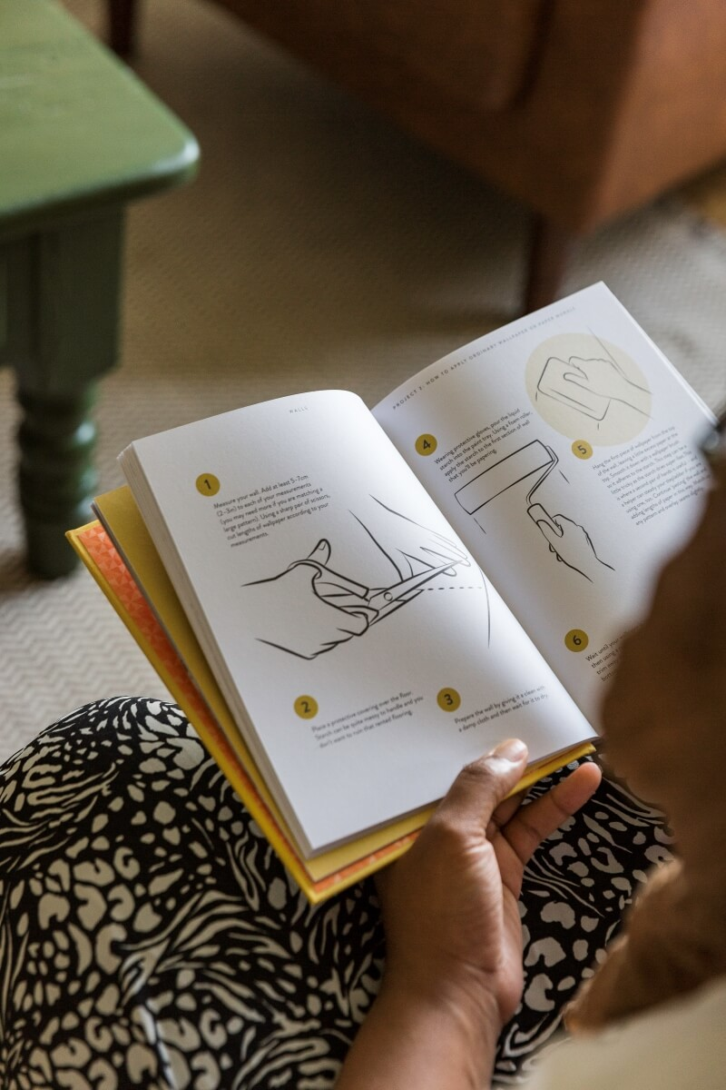 Medina grillo opening a section of Home sweet rented home book to show illustrated diy project