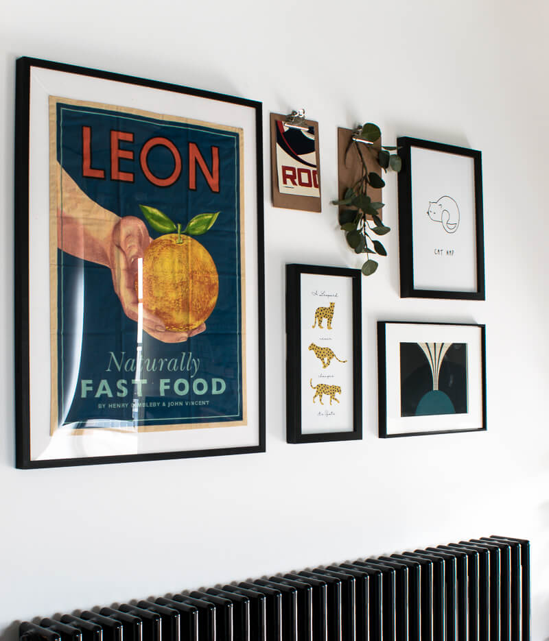 Gallery wall above radiator with LEON tea cloth insert