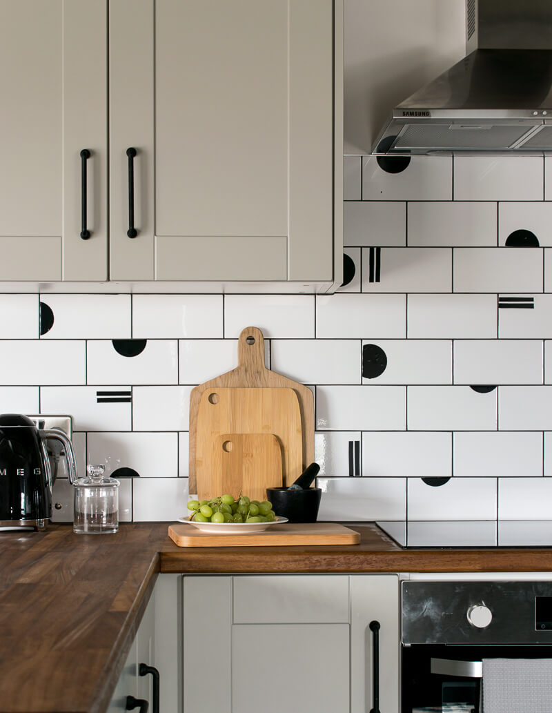 Kitchen tiles in furnished rental covered with semi circles cut from fablon paper