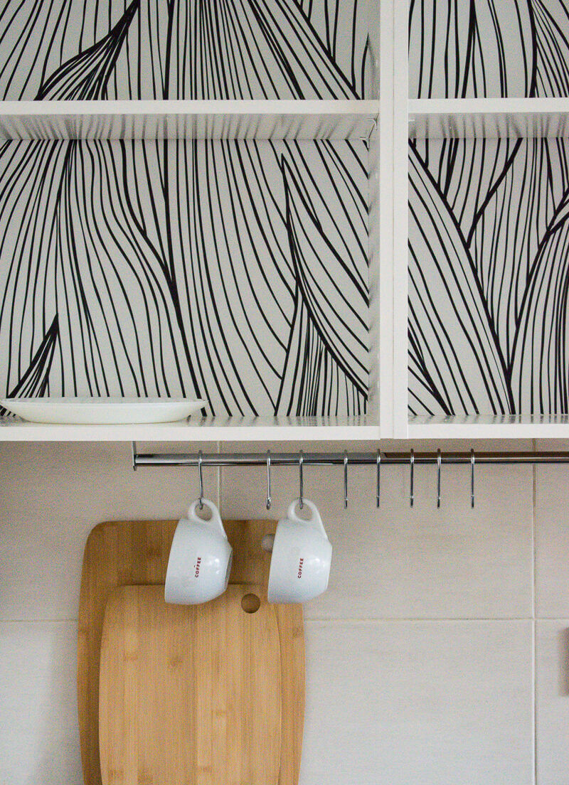 Close up image of monochrome wallpaper inside of the kitchen cabinets with chrome rail underneath