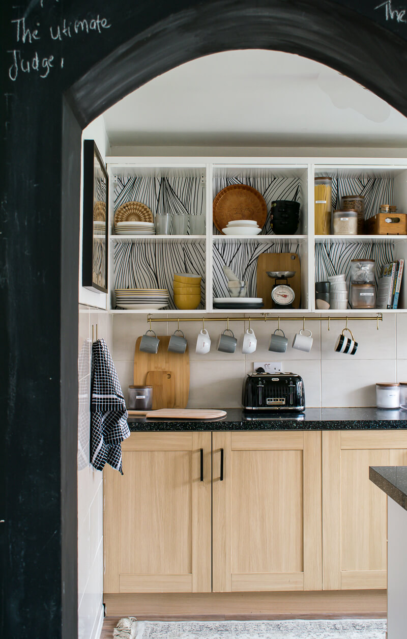 A look into thenkitchen with open plan top shelving and monochrome wallpaper applied to the backing of cabinets