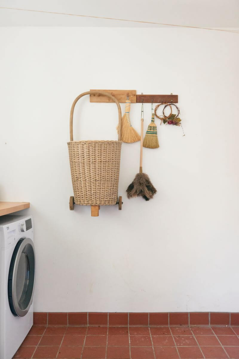 Peg hooks with broom hanging in the utility room