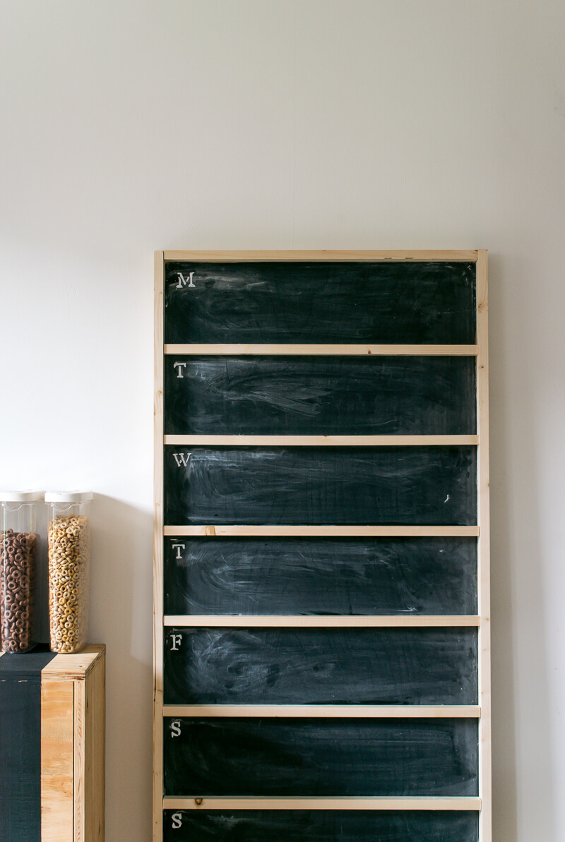 Diy chalkboard menu leaning against the wall next to a striped cabinet with cereal atop