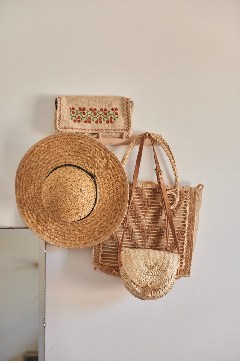 Hats and straw bags hanging on hooks
