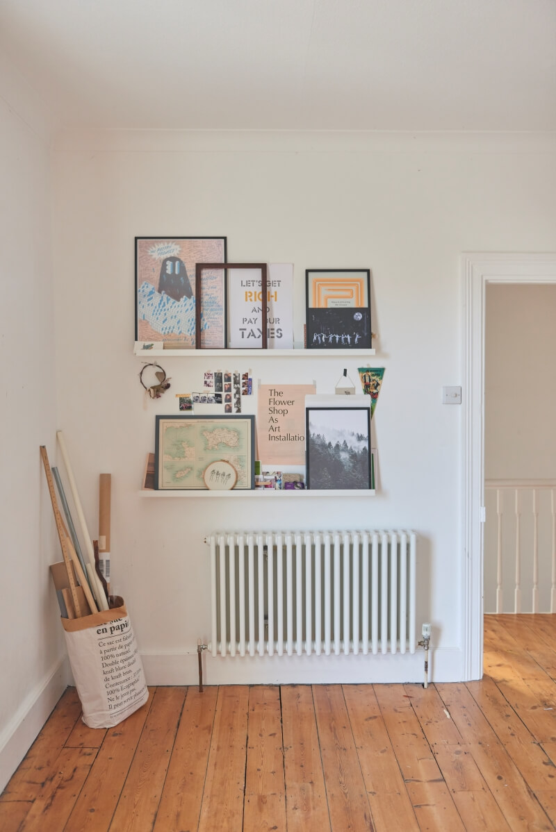 Artwork and creative items displayed on picture ledges over a radiator
