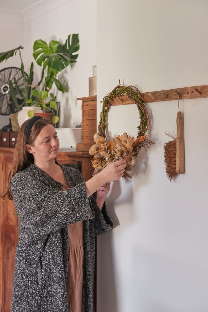 Hannah fiddling with wreath that she has made hanging on peg hook