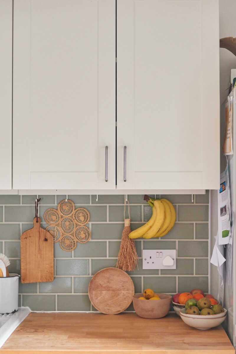 View of green kitchen tiles under top cabinets. Bowl of fruits on countertops