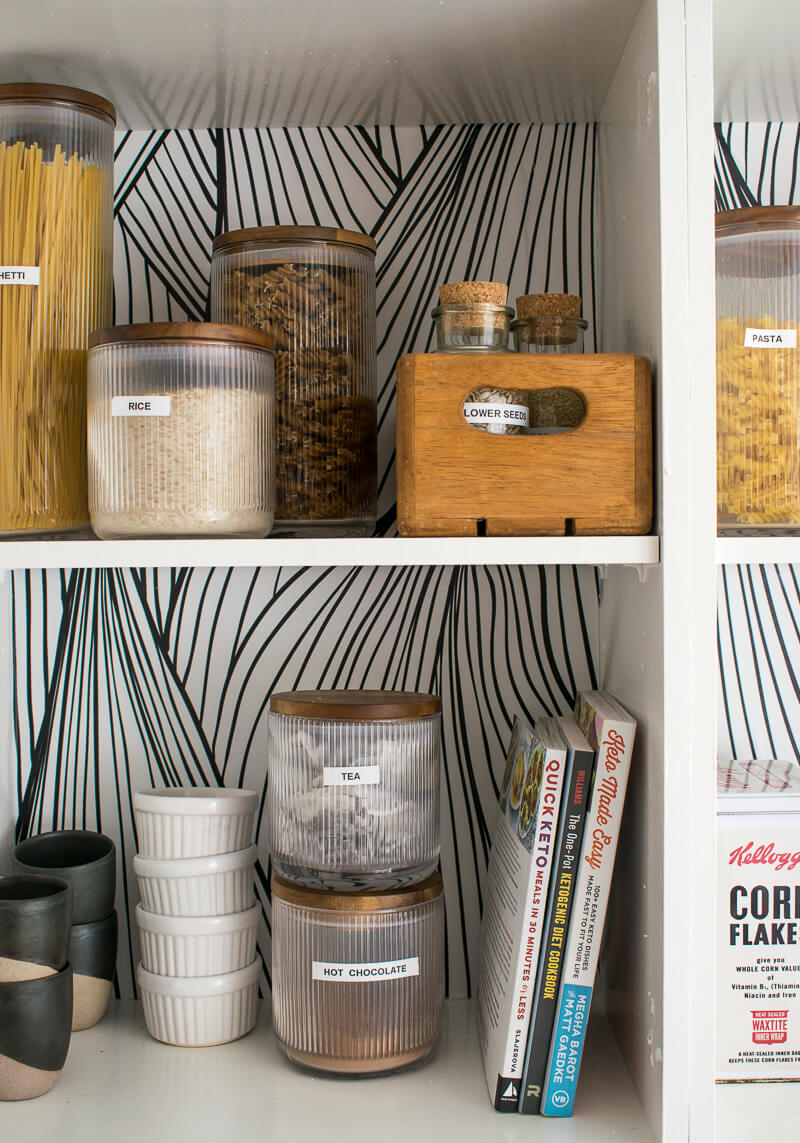 Close up of open plan kitchen cabinet without doors. Dried food stored in glass jars on the shelf