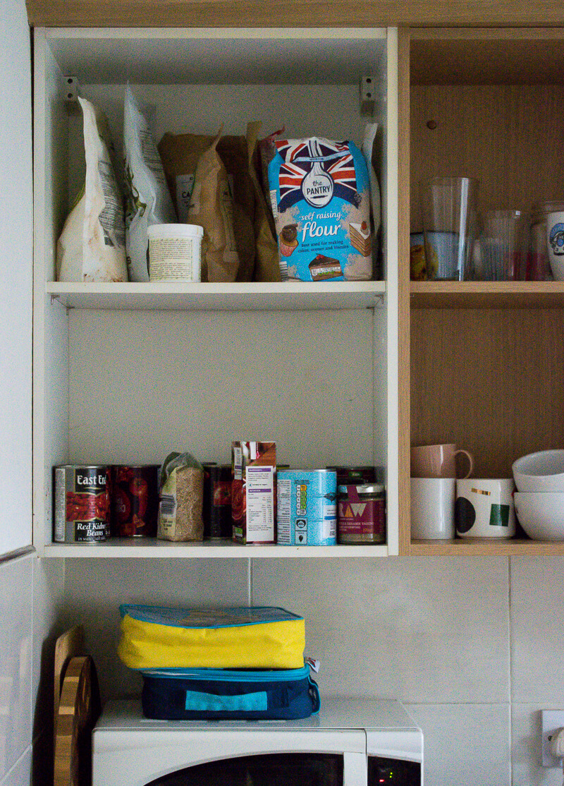 Image of cabinets with doors removed before painting. A variety of items in the cabinets including tins, flour mugs