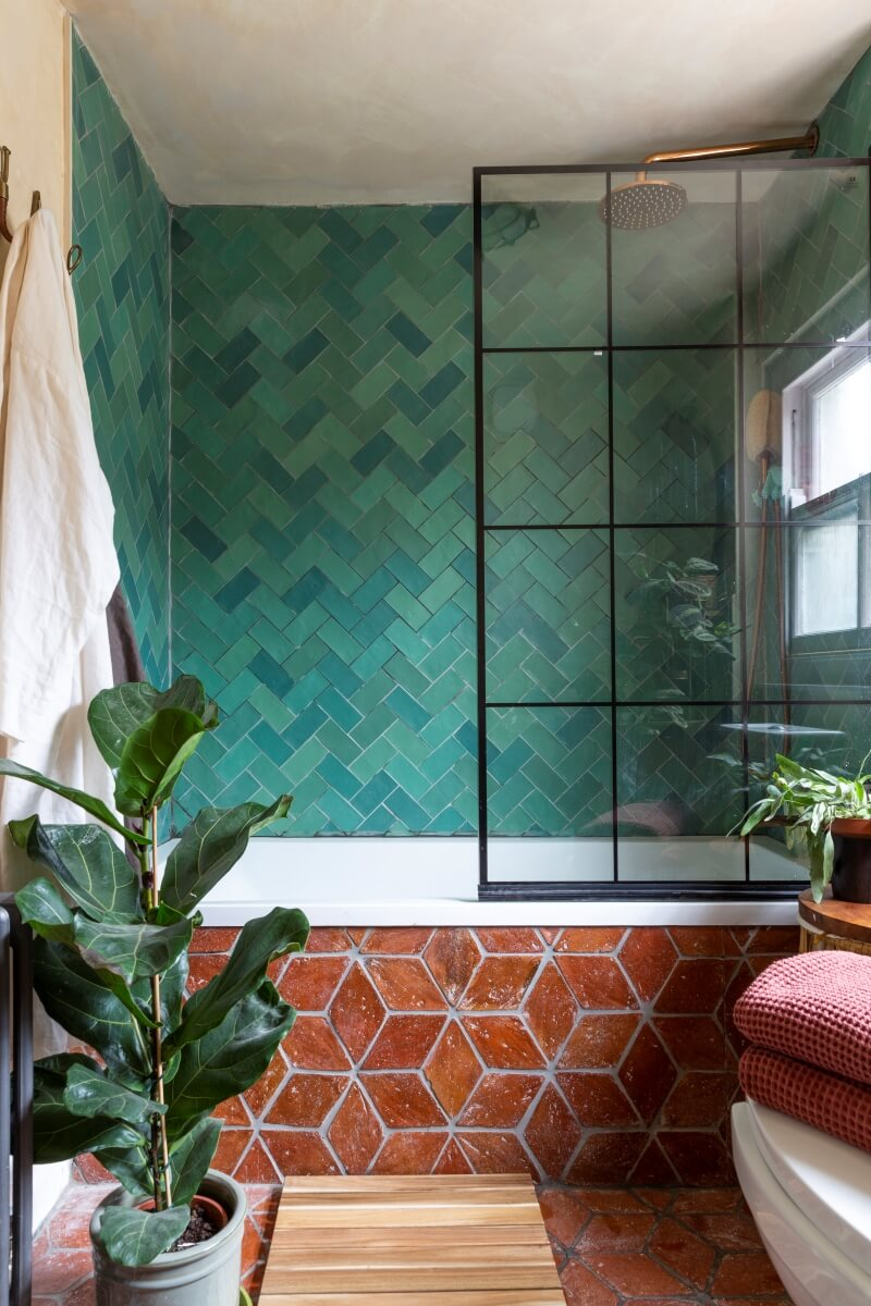 Bathroom with brick and green tile and black shower screen