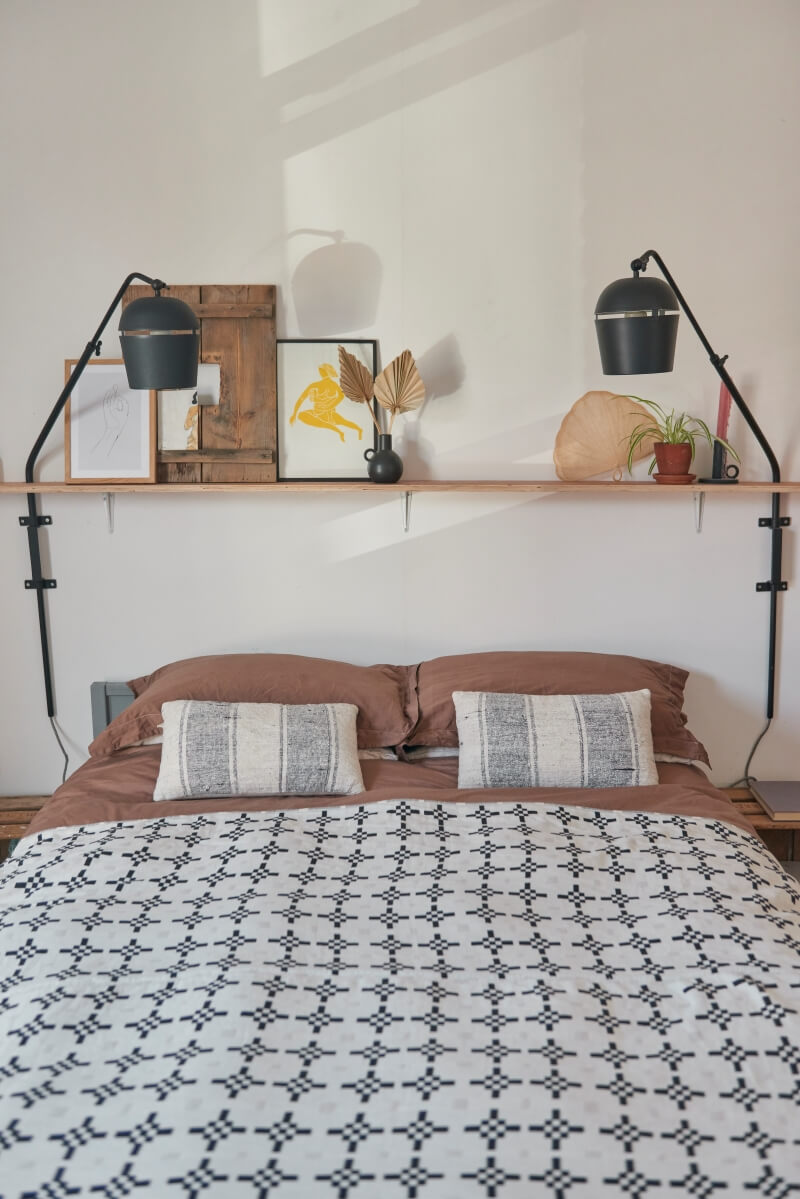 Bed with shelving across the headboard with plug in lights on wall