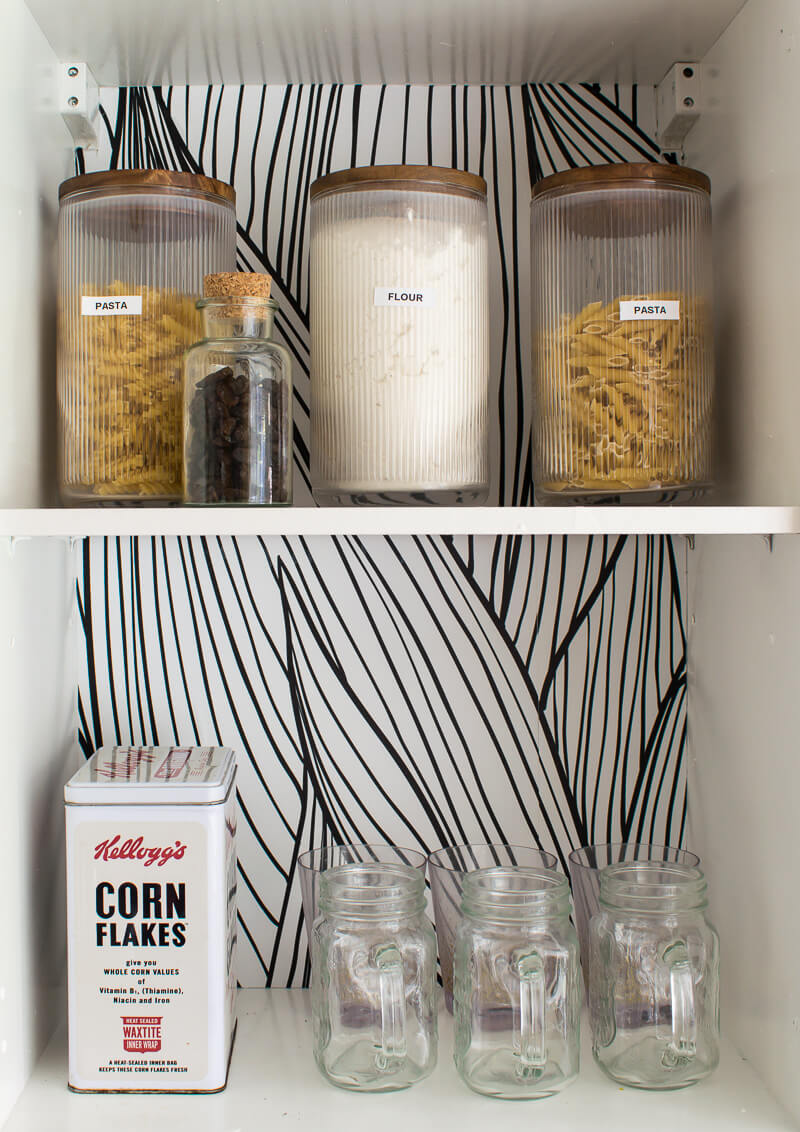 Close up of labelled glass jars on top shelf. mason glass jars and kellogs corn flakes tin on bottom shelf