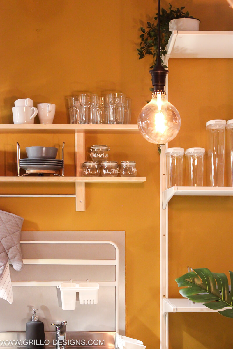 Kitchen area in living space painted ochre by dulux and various shelving in place