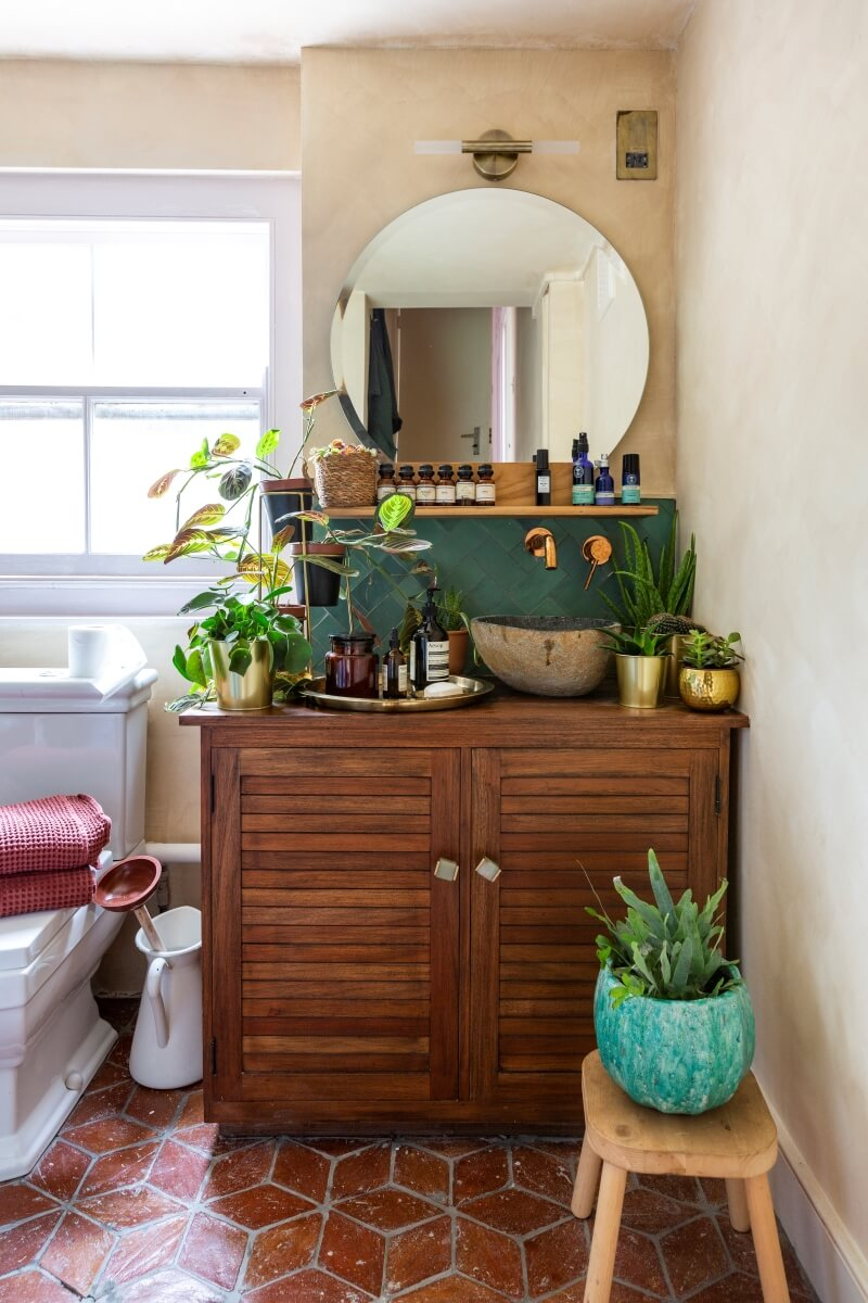 Bathroom view. Wooden cabinet and   sink with mirror atop