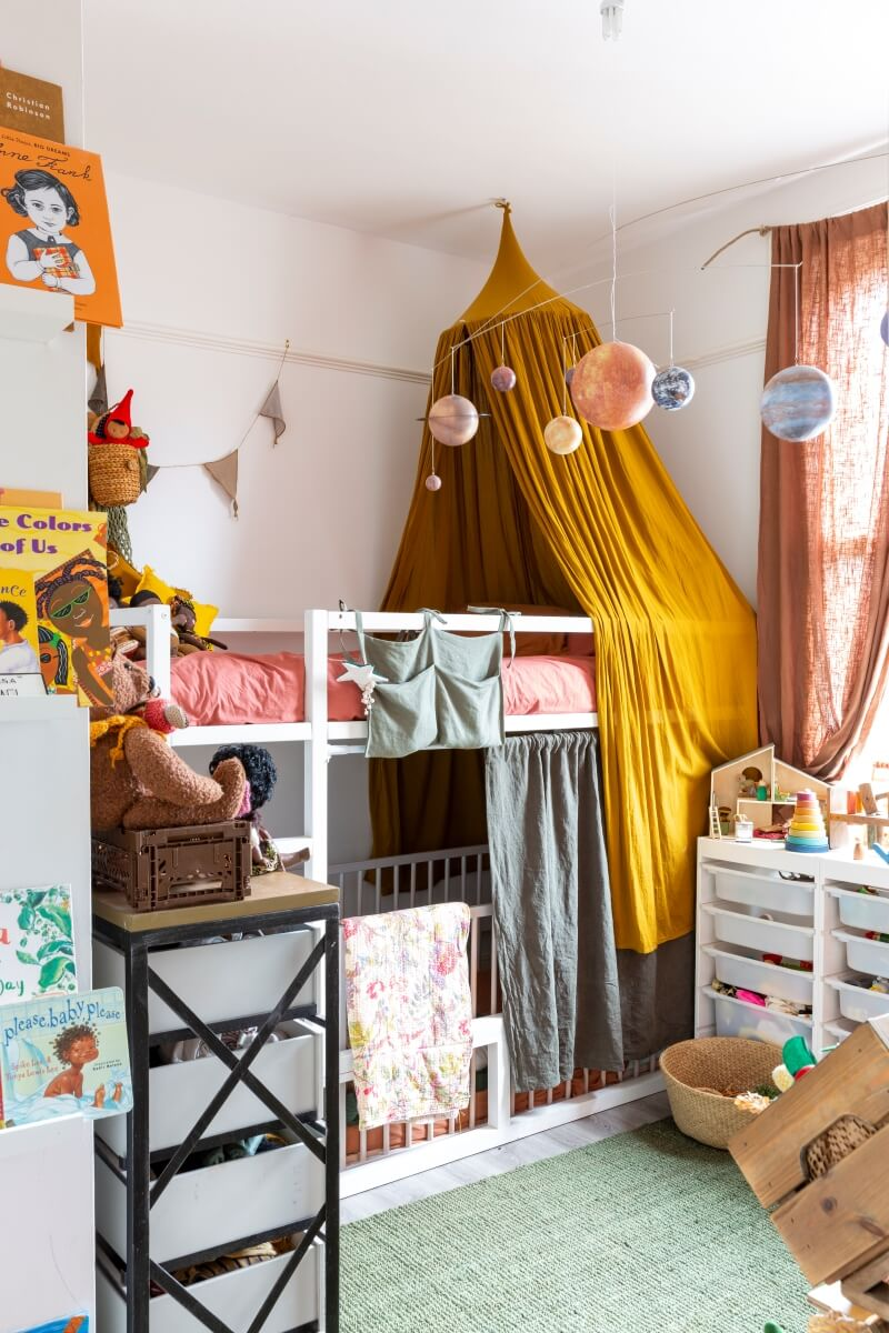 View of kids bedroom with bunk bed. Crib places under top bunk. Yellow canapy over bed
