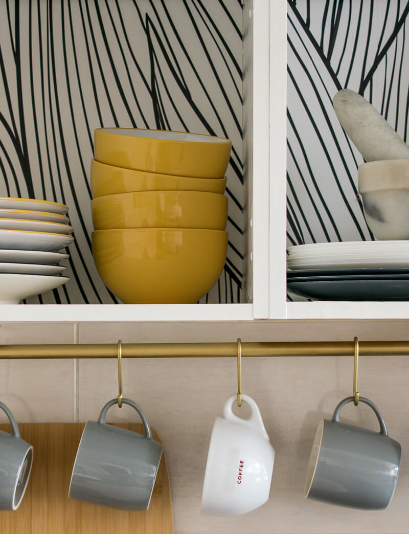 Close up image of mustard yellow stone dishware on kitchen shelves