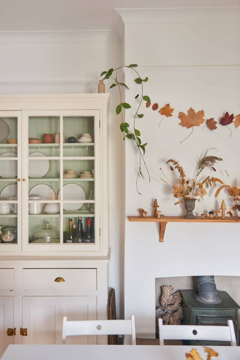 Kitchen cabinet with clear glass doors and view of autumn garland