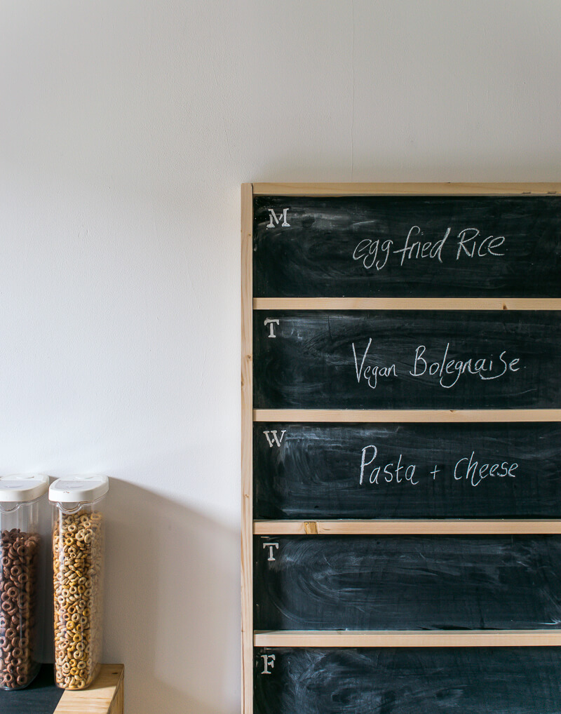 Diy chalkboard menu leaning against the wall next to a striped cabinet with cereal atop . Meals have been written on the chalkboard menu in chalk