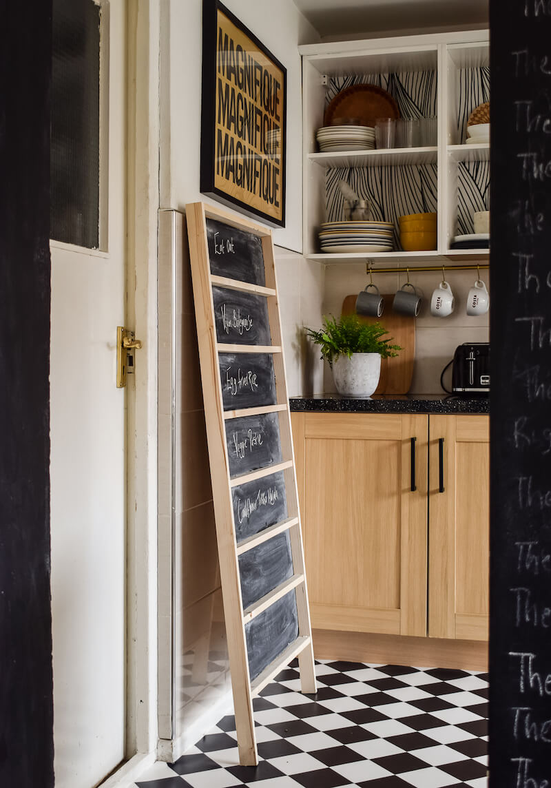 Diy chalkboard menu leaning against the wall next to a striped cabinet with cereal atop. Medina holding jamie oliver veg book in her hand