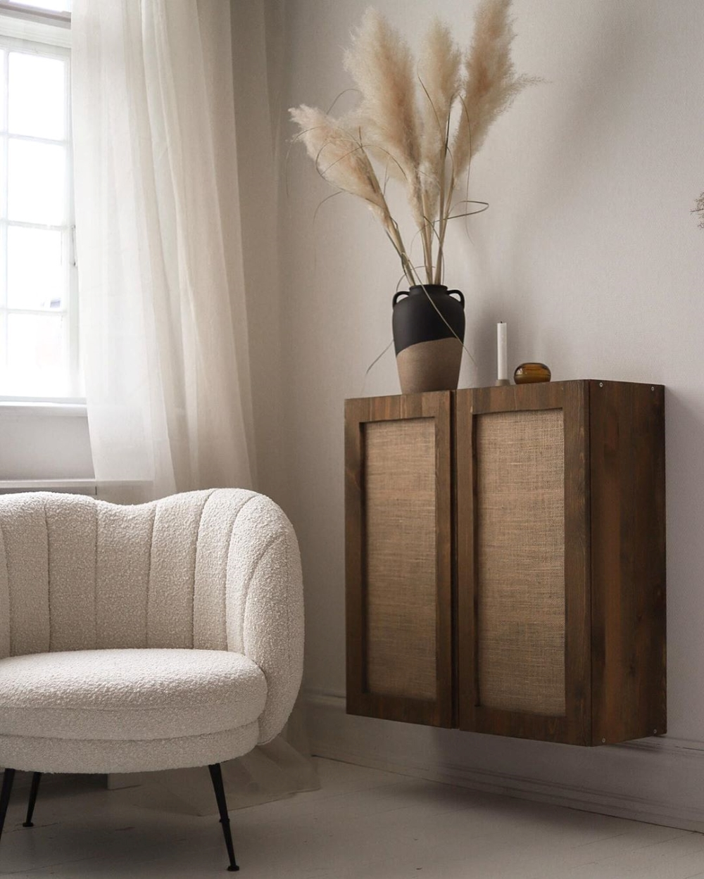 Rustic stained ikea ivar cabinet hack attached to the wall. Neutral toned armchair is situated next to the cabinet