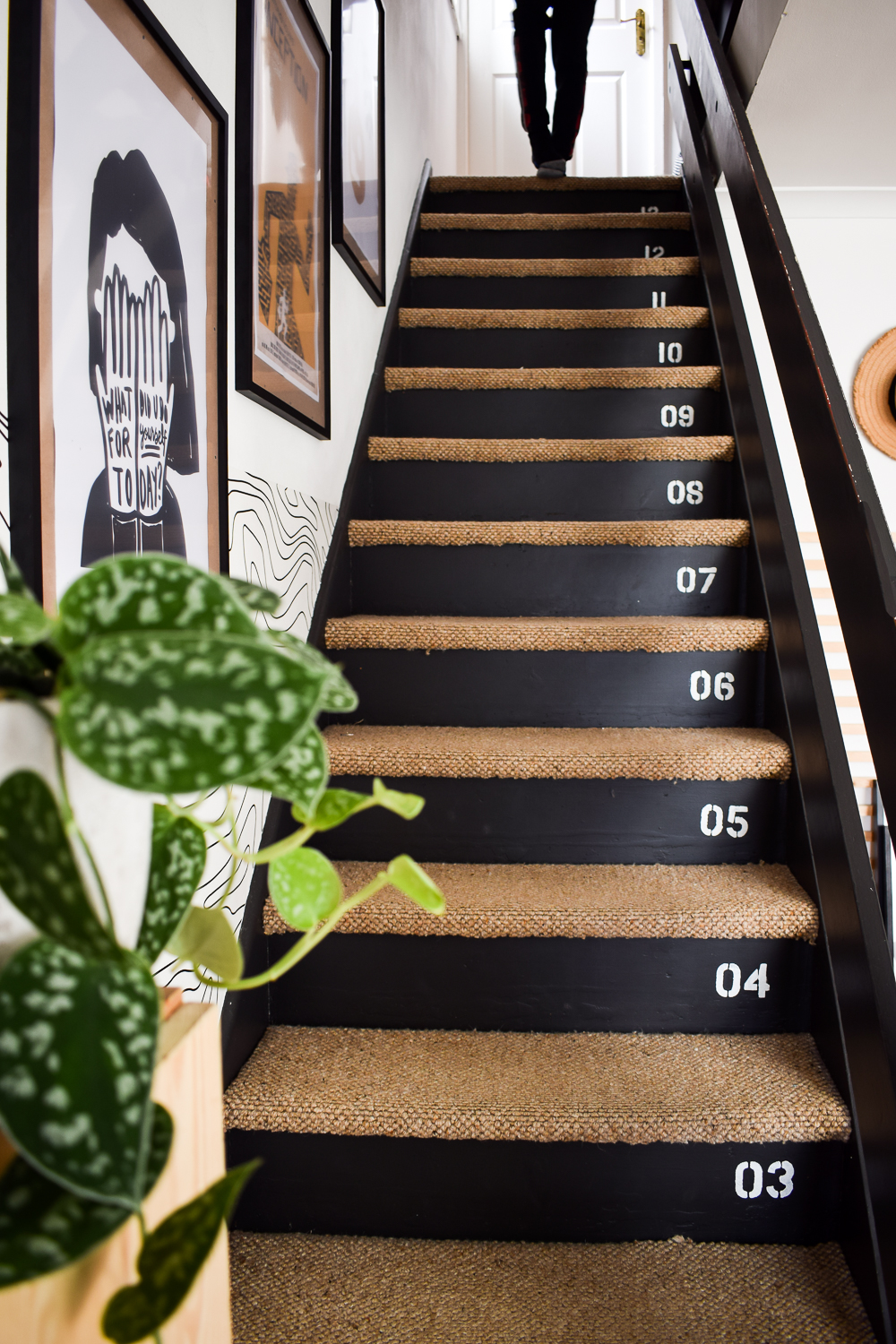 Painted black stairs with carpeted treads. Gallery wall to the left of the wall
