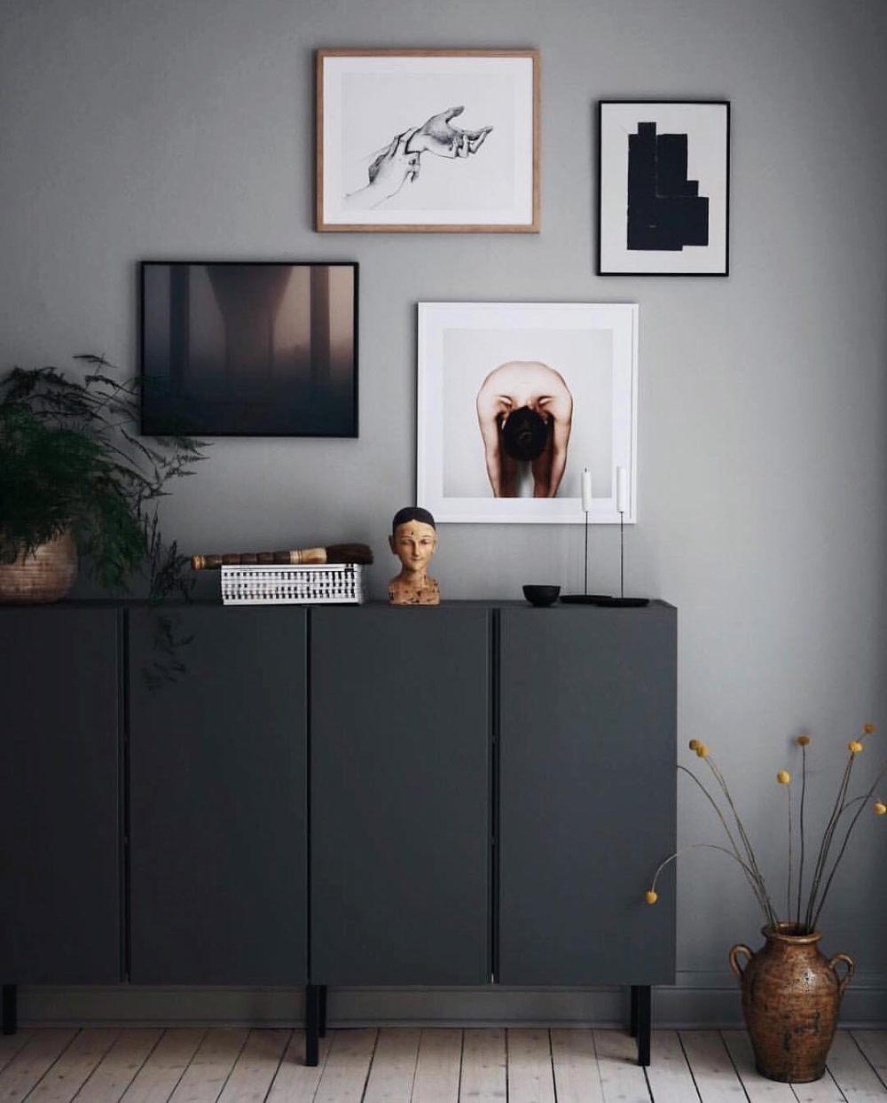 IVAR CABINETS PAINTED BLACK AND STYLED AGAINST A GREY WALL AND GALLERY WALL