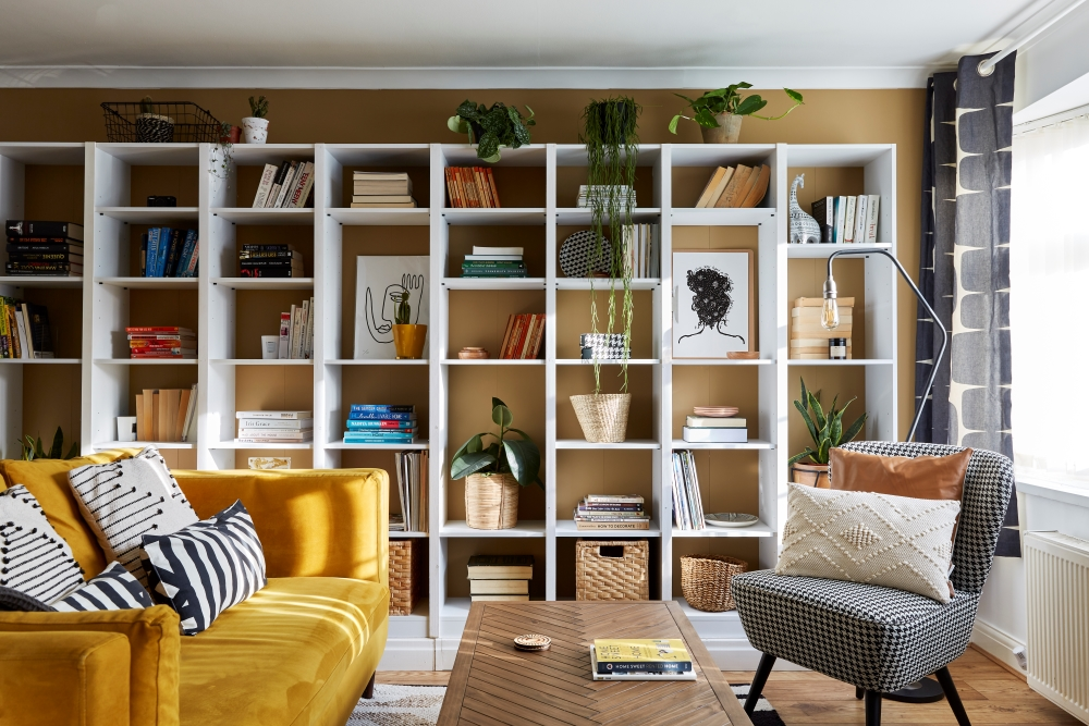 Full landscape view of a bookcase wall unit styled with plants, books, and homeware items