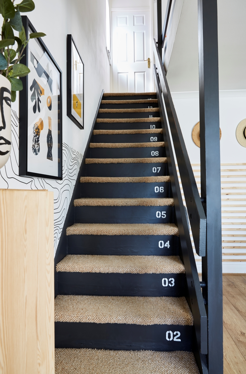 Stair case with carpeted treads and painted risers with industrial numbers