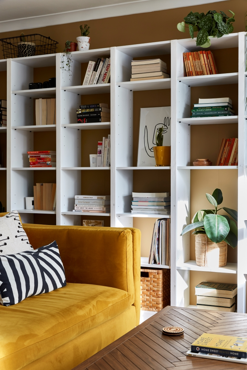 Wall to wall bookcase styled with books, images and plants