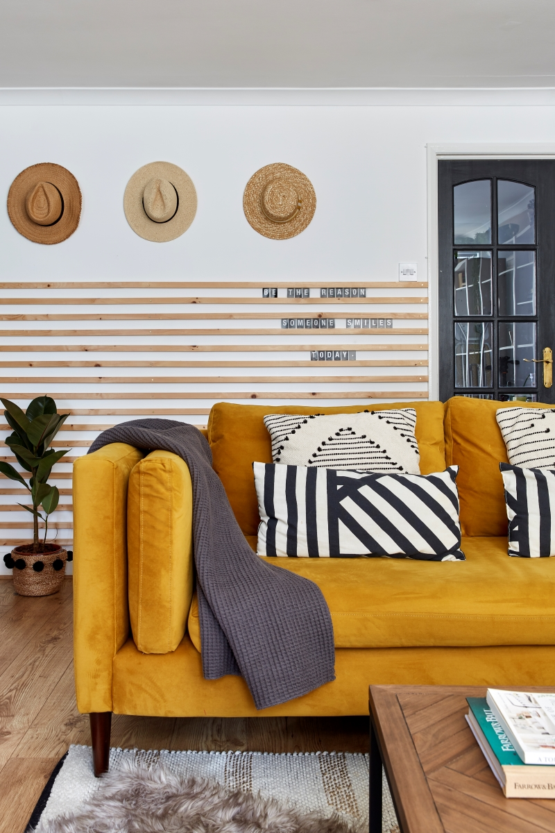 Mustard yellow sofa against a wooden panel wall