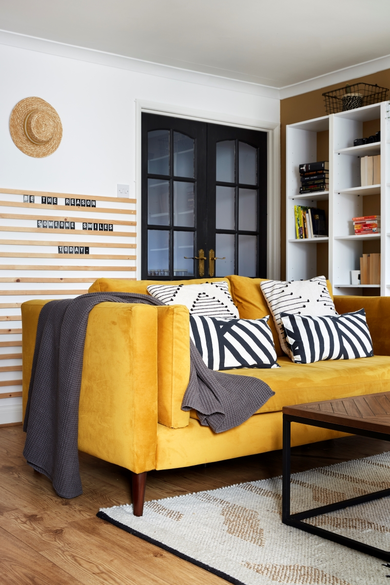 Velvet mustard sofa against the wall to wall bookcase. Monochrome cushions styled on sofa